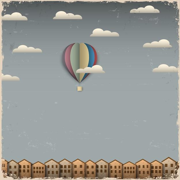 Balão de ar quente retrô e cidade de papel Vetor Premium
