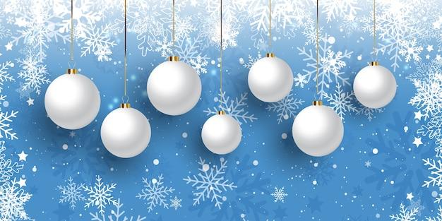 Banner de natal com enfeites pendurados em um desenho de floco de neve Vetor grátis