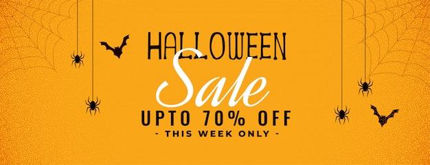 Banner de venda amarelo de halloween com aranha e teia de aranha Vetor grátis