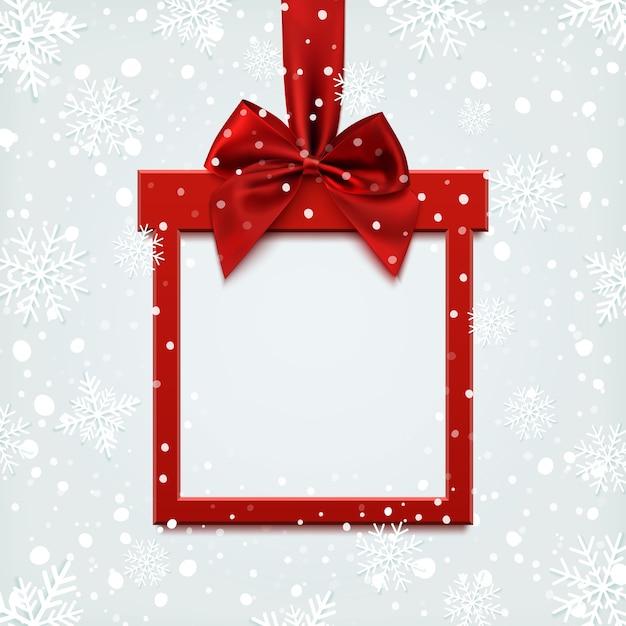 Banner do quadrado vermelho em branco em forma de presente de natal com fita vermelha e arco, em fundo de inverno com neve e flocos de neve. modelo de folheto ou banner. Vetor Premium