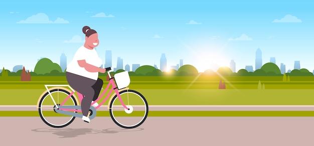 Bicicleta de equitação mulher no parque urbano da cidade menina ciclismo bicicleta conceito de perda de peso Vetor Premium