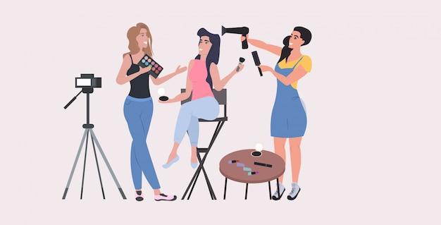 Blogueiros de beleza mostrando os tutoriais de maquiagem de tendências mais recentes, gravando blog de vídeo com câmera no conceito de blogging de tripé, mulheres segurando produtos cosméticos de corpo inteiro na horizontal Vetor Premium