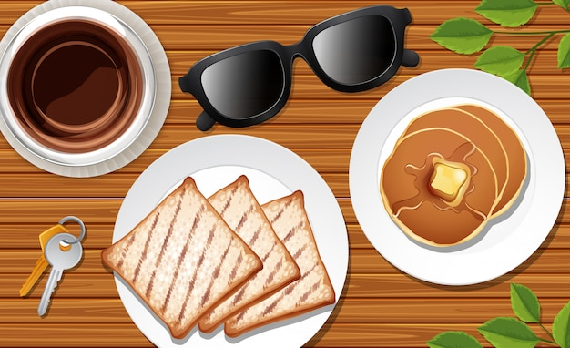 Café da manhã próximo ao fundo da mesa com alguns adereços de folhas Vetor Premium