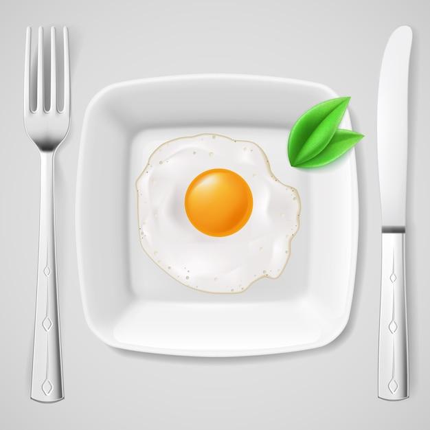 Café da manhã servido. ovo frito em prato branco servido com garfo e faca Vetor Premium