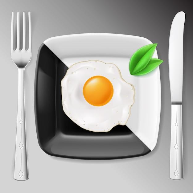 Café da manhã servido. ovo frito em prato preto e branco servido com garfo e faca Vetor Premium