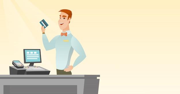 Caixa caucasiano segurando um cartão de crédito. Vetor Premium