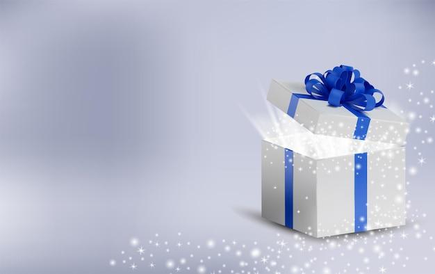 Caixa de férias aberta com brilhos brilhantes e luz mágica dentro. caixa branca em uma fita azul e laço na parte superior. Vetor Premium