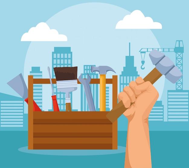Caixa de ferramentas de reparo e mão segurando um martelo sobre edifícios urbanos da cidade Vetor Premium