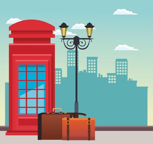 Caixa de telefone vermelha e lâmpada de rua com malas de viagem sobre edifícios urbanos da cidade Vetor Premium