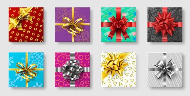 Caixas de presente com laço de fita. arcos de decoração de presentes, vista superior de férias de natal apresenta caixas. Vetor Premium