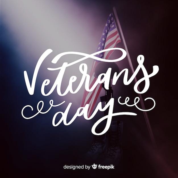 Caligrafia do dia dos veteranos com bandeira Vetor grátis