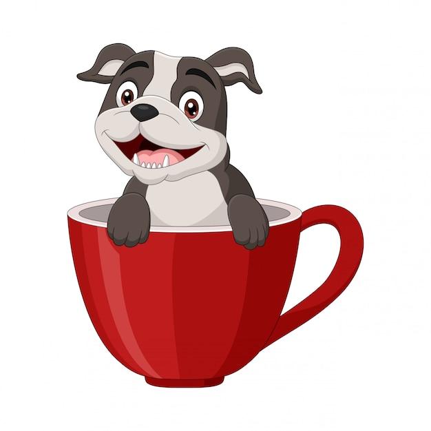 Cão feliz dos desenhos animados, sentado em um copo vermelho Vetor Premium