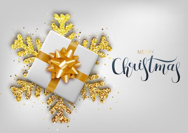 Cartão, convite com feliz ano novo. letras de escritos à mão. floco de neve de natal ouro metálico e caixa de presente em um fundo branco. Vetor Premium