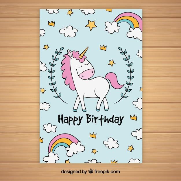 Cartão de aniversário com unicórnio e nuvens desenhadas à mão Vetor grátis