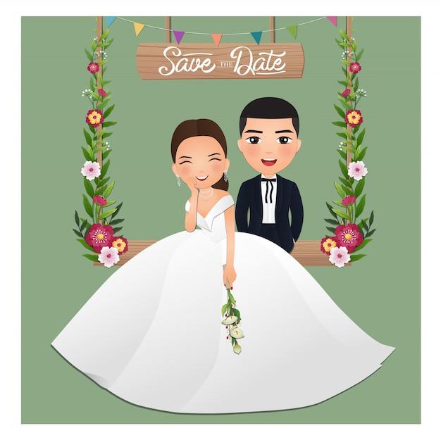 Cartão de convite de casamento - o personagem de desenho animado casal fofo dos noivos sentado no balanço decorado com flores Vetor Premium