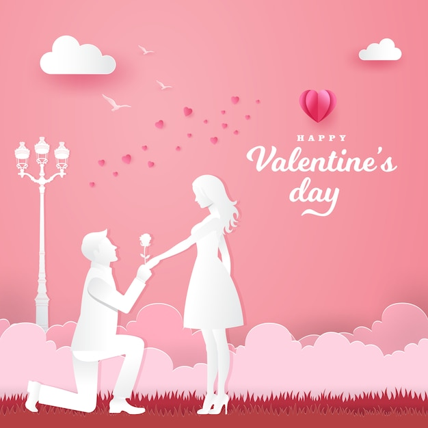 Cartão de dia dos namorados. jovem ajoelhado com a namorada e dando uma rosa no parque com coração e rosa Vetor Premium