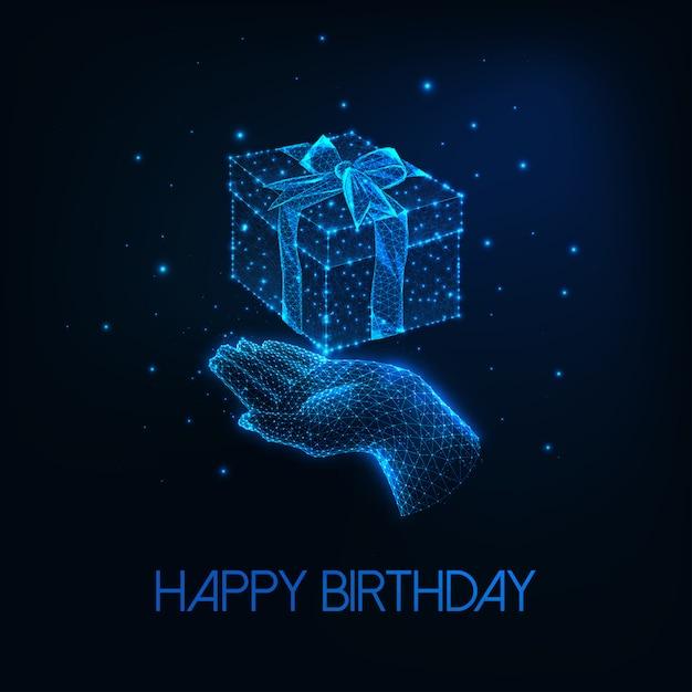 Cartão de feliz aniversário futurista com mão humana baixa poligonal brilhante, segurando a caixa de presente Vetor Premium