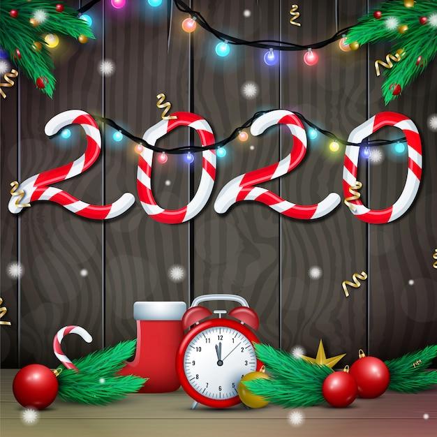 Cartão de feliz ano novo de 2020 em fundo de madeira com guirlanda de luzes cintilantes e galhos de árvores de pinheiro ou abeto Vetor Premium