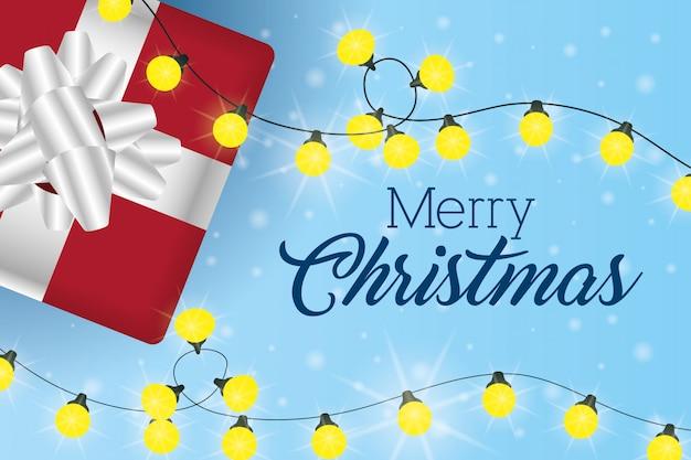 Cartão de feliz natal com presente e luzes Vetor grátis
