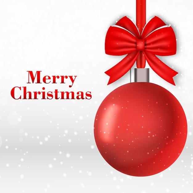 Cartão de natal com bola vermelha em flocos de neve caindo Vetor grátis