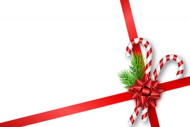 Cartão de presente de natal com laço, galhos, bastões de doces Vetor Premium