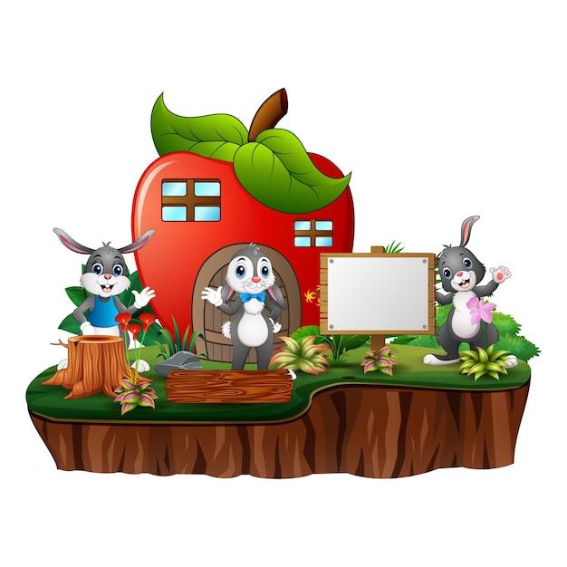 Casa de maçã vermelha com três coelhos Vetor Premium