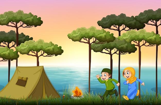Casal muçulmano acampar na floresta Vetor grátis