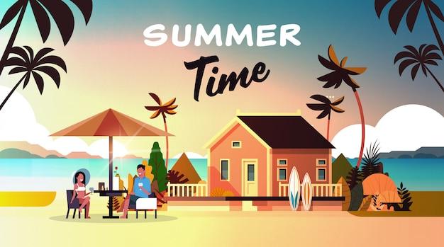 Casal verão férias homem mulher bebida vinho guarda-chuva na praia do sol casa villa ilha tropical Vetor Premium