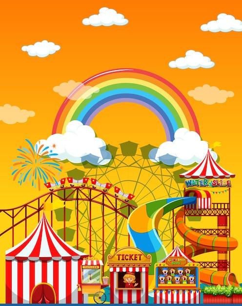 Cena de parque de diversões durante o dia com arco-íris no céu Vetor grátis