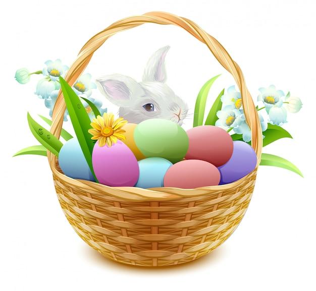 Cesta de vime com ovos de páscoa, flores e coelho Vetor Premium