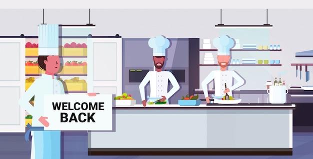Chef cozinheiro segurando bem-vindo volta placa placa coronavírus quarentena está terminando a vitória sobre o conceito covid-19 Vetor Premium