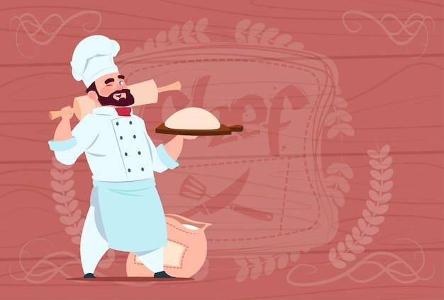 Chef cozinheiro segurando farinha e massa sorrindo cartoon chefe no restaurante branco uniforme sobre fundo texturizado de madeira Vetor Premium
