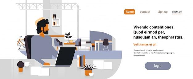 Chefe de homem árabe usando laptop local de trabalho mesa de escritório banner Vetor Premium