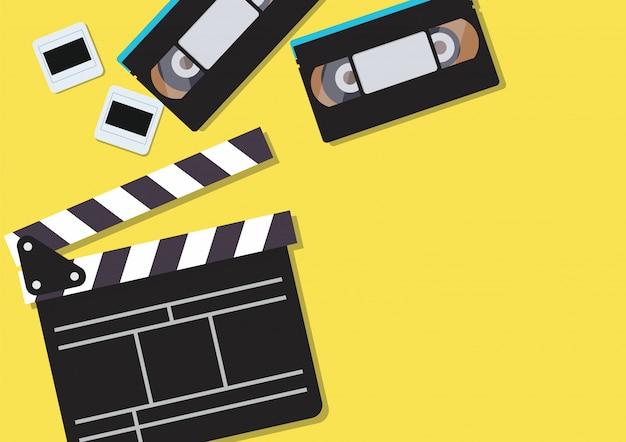 Clapper de filme e fitas cassete de vídeo em fundo amarelo Vetor Premium