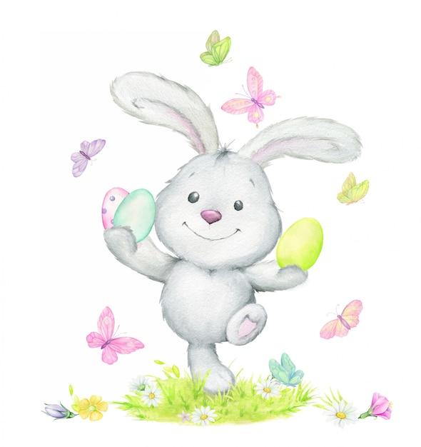 Coelho engraçado, pulando, segurando os ovos de páscoa, rodeados de borboletas. aguarela Vetor Premium