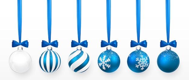 Conjunto de bola de natal transparente e azul com efeito neve e arco azul. bola de vidro de natal em fundo branco. molde da decoração do feriado. Vetor Premium