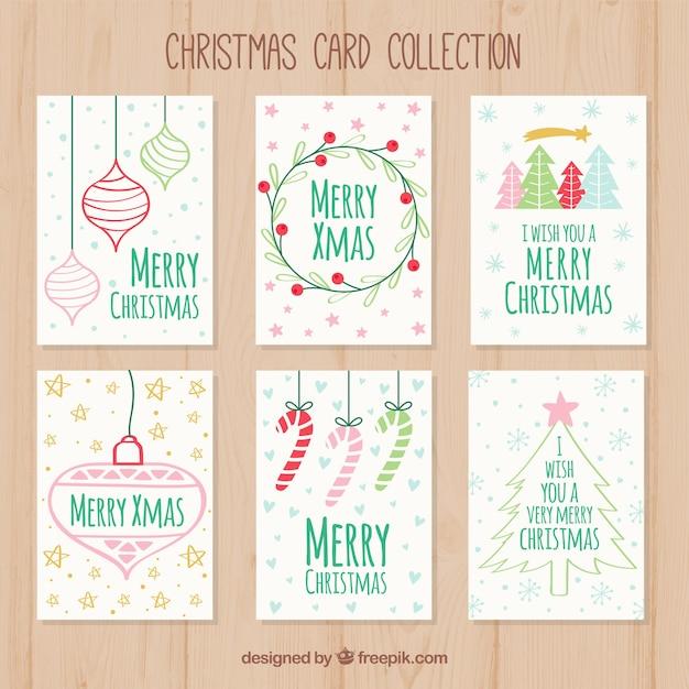Conjunto de cartões de natal desenhados à mão Vetor grátis
