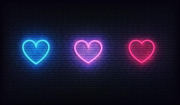 Conjunto de ícones de néon de coração. corações vermelhos, roxos e azuis brilhantes Vetor Premium
