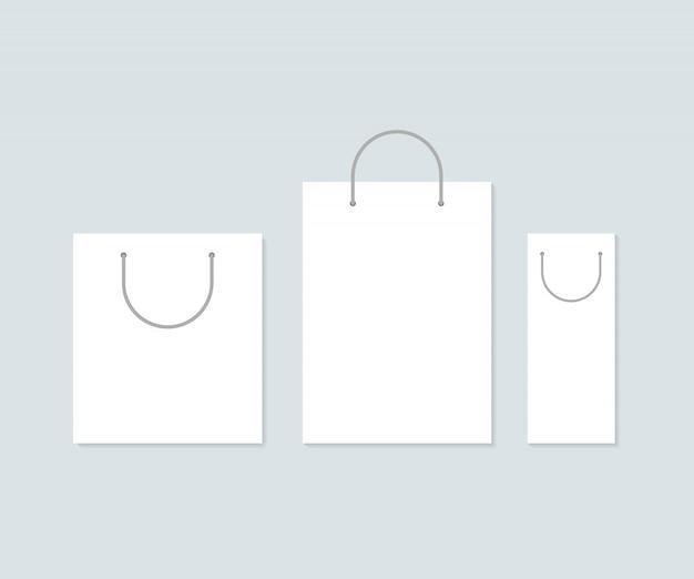 Conjunto de três sacos de compras de papel branco. Vetor Premium