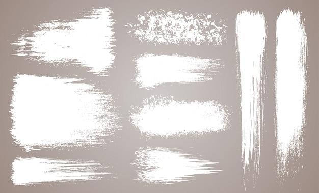 Conjunto de vetores de traçados de pincel artístico do grunge, escovas. elementos de design criativo. pinceladas de aquarela grunge ampla. coleção branca isolada Vetor Premium