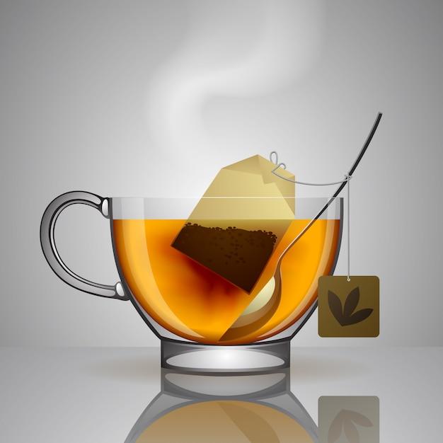 Copo de vidro transparente com saquinho de chá, colher e água quente Vetor Premium