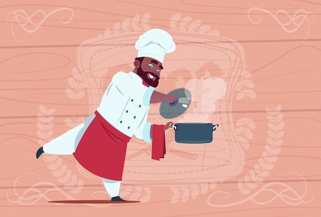 Cozinheiro americano africano, cozinheiro, segurando, panela, com, sopa quente cozinheiro sorridente, restaurante, em, branca, restaurante, uniforme, sobre, madeira, textured, fundo Vetor Premium