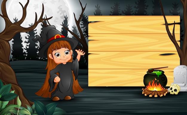 Criança feliz vestindo traje de bruxa fica ao lado da placa de madeira Vetor Premium