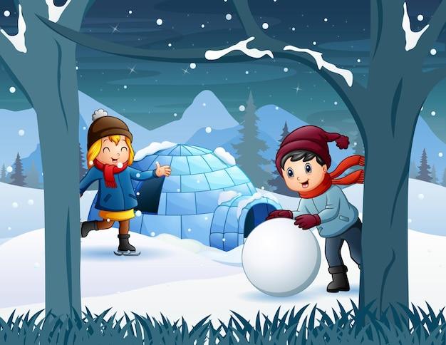 Crianças alegres brincando na neve perto da casa do iglu Vetor Premium