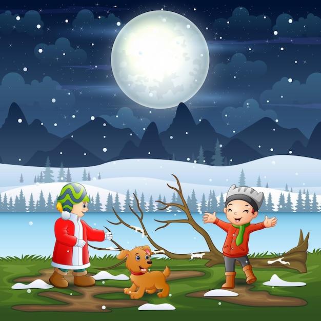 Crianças brincando na paisagem noturna de inverno Vetor Premium