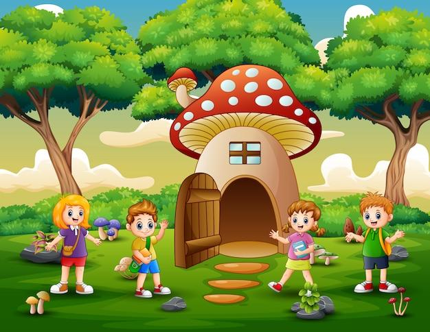 Crianças de escola felizes na casa da fantasia de cogumelo Vetor Premium