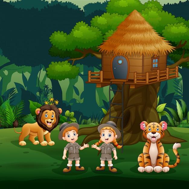 Crianças de tratador brincando com animais debaixo da casa da árvore Vetor Premium