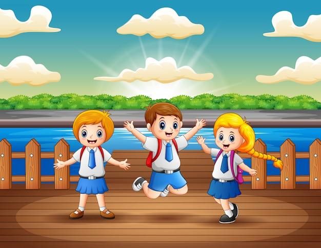 Crianças em idade escolar se divertindo no cais de madeira Vetor Premium