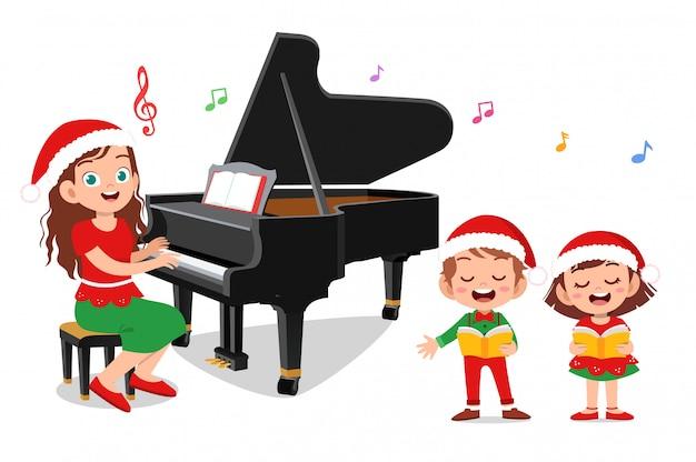 Crianças felizes cantam com piano natal Vetor Premium