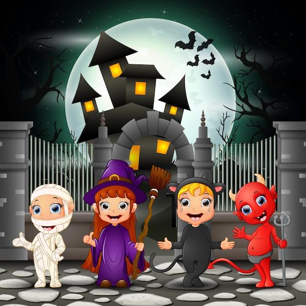 Crianças felizes de desenhos animados com fundo de dia das bruxas Vetor Premium